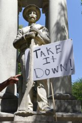 Flex Little points to a sign posted on a Confederate monument that reads