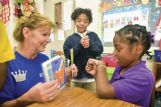Junior Auxiliary member Becky Boyd, left, teaches Joe Cook Elementary students sign language during a program Wednesday that put students in a disabled person's shoes to better understand their struggle. Kejhi Rodriguez, 7, center, does the sign for