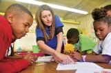 Junior Auxiliary member Meryl Fisackerly, center, teaches Joe Cook Elementary student Ankeria Harkins, 7, right, how to write her name in Braille. Ankeria is the daughter of Ashaki Moody of Columbus.