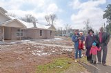 Major Andrews III, his wife, Shirley, and the couple's daughter and grandchildren stand outside their soon-to-be completed new home on Shady Street. The couple first moved to the Shady Street location in 1980, and the Feb. 23 tornado that devastated the area has done nothing to change their mind about staying in the neighborhood.