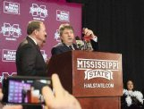 Mike Leach rings a cowbell during his introductory press conference Jan. 10 in Starkville alongside MSU President Dr. Mark E. Keenum.