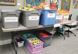 Bins at the Columbus Arts Council Tuesday fill with supplies for Art Reach boxes.