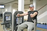 YMCA program director Salem Gibson works out on equipment at the downtown Columbus Y on Thursday evening. Gibson said people often set unrealistic goals or become too intimidated to go to the gym, which keeps them from getting in shape. He recommended