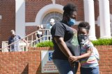Carshena Connor hugs Cheyanne Conner-McKinstry, 7, during a protest demanding Lowndes County Board of Supervisors President Harry Sanders' resignation on Wednesday on the Lowndes County Courthouse lawn. District 5 Supervisor Leroy Brooks asked for Sanders' resignation and said that if he did not give it, people should gather again during the next supervisor meeting on June 30.