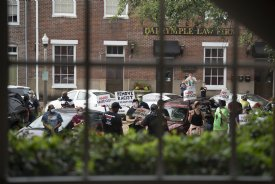 Protesters can be seen through the window of the Lowndes County Courthouse as they demand District 1 Supervisor Harry Sanders' resignation during the supervisors meeting on Monday. This was the third time a crowd has gathered in response to racist comments Sanders made about African Americans after the June 15 supervisors meeting. / Photo by: Claire Hassler/Dispatch Staff