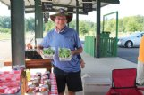 Charles Speed holds up baskets of fresh okra at the Hitching Lot Farmers' Market at Second Avenue and Second Street North in Columbus Monday. Speed and his wife Paula have Speed's Farm in Ethelsville, Alabama.