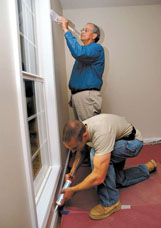 Fairview Baptist Church Minister of Senior Adults and Missions Tommy Gillon, standing, paints window trim at the Habitat  house Tuesday. Volunteer Adam Martin applies caulk.