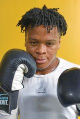 Zion Reed pauses for a portrait between throwing jabs at the punching bag during practice on Thursday at Miller's Boxing and Taekwondo Gym in Columbus. On Oct. 18, Reed participated in a three-round practice bout at Trotter Convention Center, which he won.