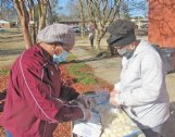 Tasha Beckum, a Starkville Strong volunteer, and Santee Ezell, a Black Girls Rock volunteer, prepare food packages for distribution Monday at the J.L. King Center in Starkville. Volunteers gave out 100 hot meals and 100 food boxes as part of a Martin Luther King Jr. Day of Service event.