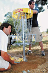 Local disc golf fan Kenneth Gustine holds a disc golf basket up straight while Chip Strain, president of the Whispering Pines Disc Golf Club, makes concrete for it to settle. They did this 18 times to make a new disc golf course at Propst Park Saturday.