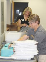 Junior Auxiliary member Heather Brignac, foreground, and Ashli Dunn sort plastic boxes that will be filled with art supplies for pre-K through fifth-grade students.