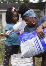 """Omini Parks and her daughter Gibson, 5, prepare to repot tomatoes on Thursday outside their home in Starkville. Gardening is a fun activity for the two to do together """"when Gibson listens!� Parks said."""