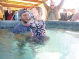 First Pentecostal student pastor Craig Blaylock baptizes 5-year-old Kinsey Lambert Sunday morning as her father, Joseph Lambert, raises his hands in celebration in the background. The church was destroyed by Saturday evening's tornado, but the church proceeded with the planned baptisms anyway, using a portable hot tub provided by Vibrant Church as a baptismal.