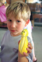 """Six-year-old Davis Lancaster of Starkville holds a squash """"monkey� at the West Point Farmers' Market. Davis' parents are Eric and Anna Lancaster."""