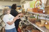 Volunteer Judith Moore, in the foreground, and Habitat ReSale Store staff member Chelcee Ezell arrange baskets for display Wednesday.