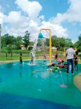 Children enjoy the new water bucket feature at the J.L. King Memorial Park splash pad on a hot summer day. The water bucket is a Pilot Club of Starkville project.