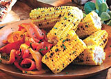 Grilled sweet peppers and corn on the cob hot off the grill are stand-out sides for a Fourth of July celebration. Think outside the traditional cook-out box with recipes from the pages of Bon Appétit magazine.