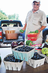 Archie Noy of Columbus unloads fresh blueberries and other homegrown produce at the Hitching Lot Farmers' Market Monday in Columbus.