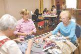 Volunteers Karen Benglen, Marian Hazard and Beth Jones pin trim on dresses, for necklines and straps.