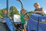 Riley Jaudon, 2, and Eli Jaudon, 6, play with the buttons on a tractor during the United Way of Lowndes County's Little Hands, Big Trucks event at the Soccer Complex in Columbus Saturday morning.