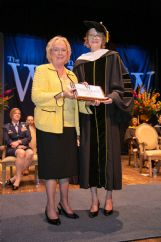 Connie Kossen, left, presents Erin Kempker with the Kossen Faculty Excellence Award at The W's Commencement May 11.