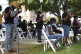People bow their heads and close their eyes during a Kingdom Vision International Church worship service on Sunday outside the Lowndes County Courthouse. White chairs were spread out on the lawn in front of the stage for people to sit. Others brought their own lawn chairs or stood in the shade of trees or near their cars.
