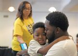 Pierre Beard holds his son, Pierre Beard Jr., 4, while waiting for the final two ballot boxes from the Hunt precinct to be counted Tuesday night at the Columbus Municipal Complex. Beard was already ahead 149-68.