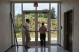 From left, Sumner Davis and Wes Gordon, both members of the school board, look outside during a tour of The Partnership School on Wednesday in Starkville. Superintendent Eddie Peasant said the pile of dirt outside will be moved onto a playing field before construction is done.