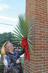 Rachel George attaches palm fronds at the entrance of St. Paul's Episcopal Church in Columbus April 3, in advance of Palm Sunday. In-person services may be on hold, but worship is not.