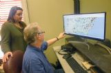 Allen McBroom shows Oktibbeha County Emergency Management Director Kristen Campanella a website that allows amateur radio users to use a digital signal for communication and shows users from around the world.