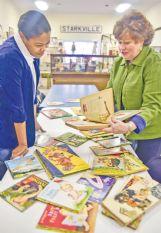 Shamera Brumfield, left, and Hellen Polk look through Little Golden Books at the museum Wednesday.
