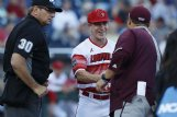 Louisville Cardinals head coach Dan McDonnell greets Mississippi State Bulldogs head coach Chris Lemonis as home plate umpire Jeff Hinrichs looks on prior to the game in the 2019 College World Series on June 20 at TD Ameritrade Park.