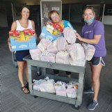 Alison Alexander, Jan Miller and Amber Brislin load a cart with some of the supplies purchased for Art Reach boxes.