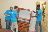 Staff members, from left, Matthew Richards, Ethan Criddle and Kalib Young move donated furniture into position Wednesday in preparation for shoppers at the Habitat for Humanity ReSale Store in Columbus.