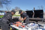 Jarriel Jones and Devaris Hayes cook hot dogs for community members at Carter's Funeral Home in Columbus Sunday afternoon. Jones and Hayes both work for Carter's.