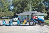 Curtis Bilbo, right, drives a tractor pulling a makeshift train through a parking lot near West Point City Park on Saturday. The train was a socially distant substitute for the hayride usually offered at West Point's annual Makin' Hay Day, which combined with the city's farmers' market and the annual Prairie Arts Festival to create