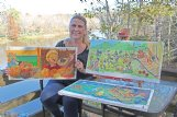 Jeanette Jarmon of Columbus displays several original paintings of her illustrations for