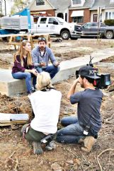 An HGTV film crew captures Amanda Kelly and Austin Shafer discussing renovations outside the house on Worley Street featured in the television show.