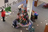 Members of the International Spouses Group from Columbus Air Force Base decorate their adopted tree at the Columbus-Lowndes Public Library Monday morning.