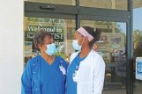 Mother and daughter Jewell Jones, left, and Alexis Jones don masks before entering the Baptist Memorial Hospital-Golden Triangle Outpatient Pavilion Wednesday.