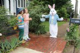 Cash Castro, 9, and his sister Lola Castro, 11, are greeted by the Easter Bunny as the seasonal visitor (Midge Maloney) strolled past their Southside house in Columbus Wednesday. The siblings' parents are Japa and Alicia Castro.