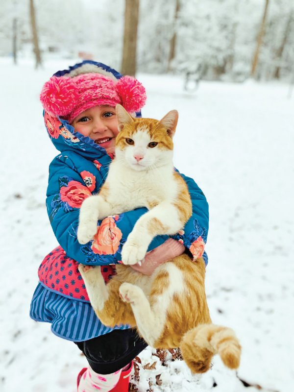 Olivia Brackin, 5, and Orangie the cat play in the snow. Olivia's parents are David and Leah Brackin. / Photo by: Courtesy photo