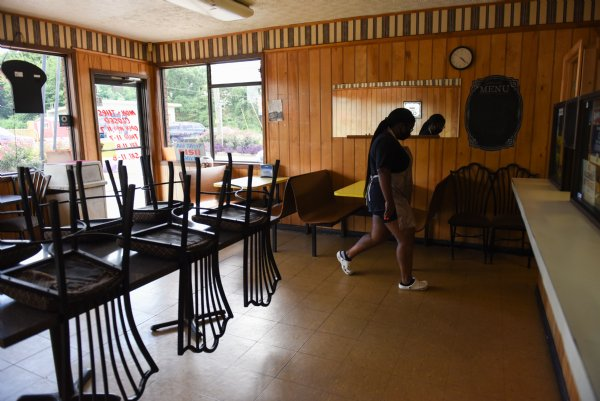 Carolena Graham, 16, walks through the empty dining room back to the kitchen after bringing out a curbside pickup order on Friday at Skeet's Hotdogs in Columbus. Sylvia Graham, owner of Skeet's Hotdogs, said business has been up throughout the pandemic. She's owned Skeet's for 12 years so she knows the buying patterns of her customers. She attributes increased business to people receiving unemployment and stimulus checks. / Photo by: Claire Hassler/Dispatch Staff
