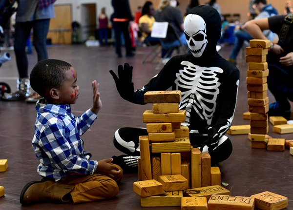 Ayden Leach, 3, left, gives a high-five to Conner Bastow, 12, during Art in the Park Oct. 26 at the Starkville Sportsplex. / Photo by: Jennifer Mosbrucker/Dispatch Staff