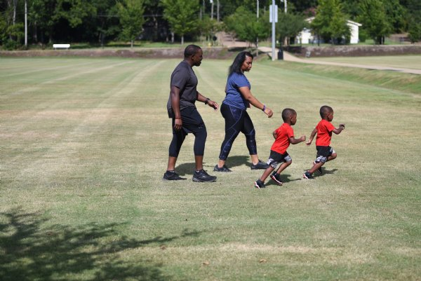 Justin and Kasenda Martin walk with their sons, from left, Bryson and Landon, both 3, on Saturday at the River Walk Soccer Complex in Columbus. Much like his mother brought him, Martin brings his own children to the fire station sometimes. He said they absolutely love it, especially Landon. / Photo by: Claire Hassler/Dispatch Staff