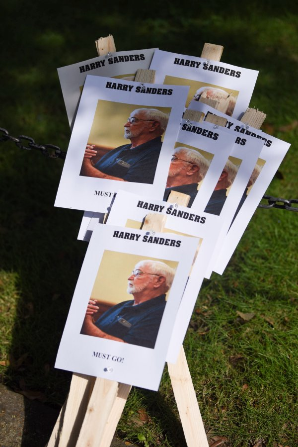 """A pile of signs that read """"Harry Sanders must go!"""" sit on the courthouse lawn before the Equality and Justice March on Saturday in Columbus. The signs, which also feature a photo of Harry Sanders, were distributed to protesters before the march. / Photo by: Claire Hassler/Dispatch Staff"""