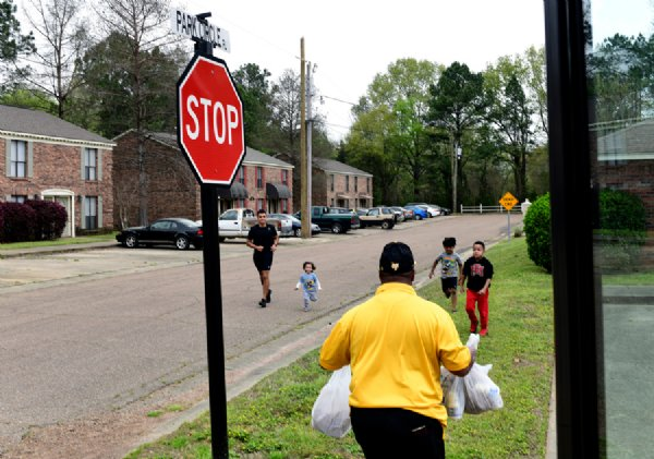 From left, Eddie Marroquin, Matthew Marroquin, 2, Vihaan Sankar, 5, and Kylan Tallie, 7, run to the school bus to grab a lunch from Carlos Kemp on Sunday in Starkville. Armstrong Middle School distributed 225 lunches to students Friday. Some version of meal deliveries will be available to students while school is out of session until April 17 to prevent the spread of COVID-19. The program is funded by the Summer Food Service Program through the U.S. Department of Agriculture Food and Nutrition Services. / Photo by: Jennifer Mosbrucker/Special to The Dispatch