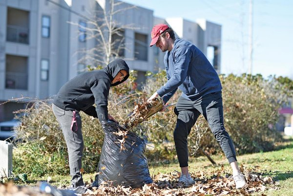 Jared Brock, left, and Jared Kimes help clean up Odd Fellows Cemetery in Starkville during their day off from school for Martin Luther King Jr. Day on Monday. Hundreds of volunteers participated in a Day of Service to honor King's legacy. / Photo by: Austin Frayser/Special to The Dispatch