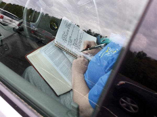 A churchgoer makes notes as she listens to the sermon through her car's radio. / Photo by: Jennifer Mosbrucker/Special to The Dispatch
