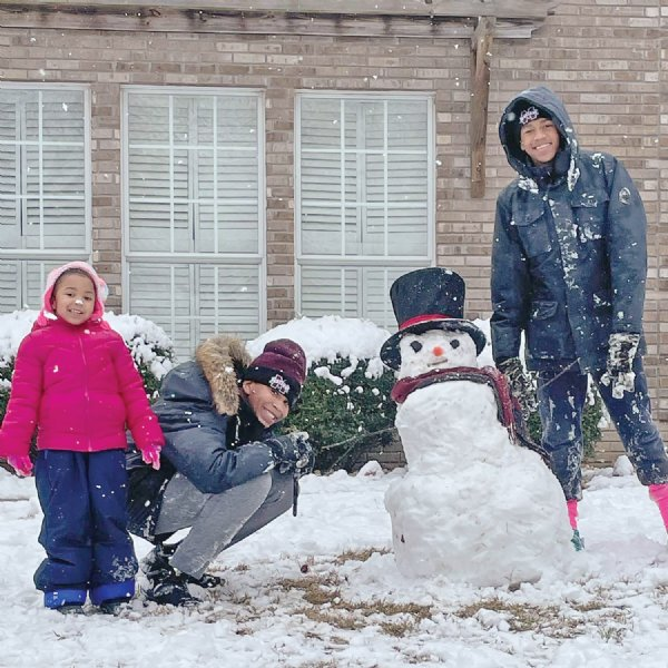 Cayleigh, Chase and C.J. Gathings enjoy making a snowman outside their home in Columbus. About two inches of snow accumulated in much of the region, but above freezing temperatures in the afternoon saw it quickly melt away. / Photo by: Courtesy photo